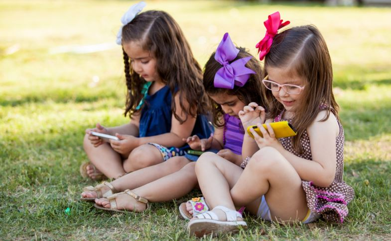Cute Little Girls Playing With Their Smartphones Ignoring One Another In A Park - Social Media And Technology Effect